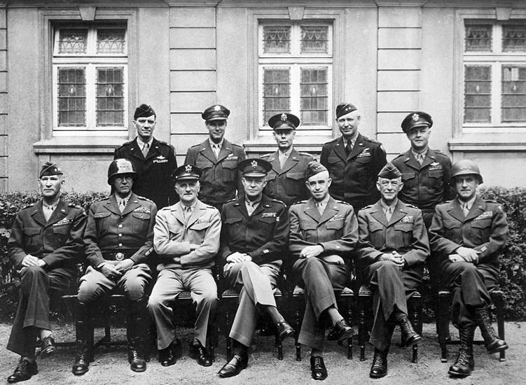 Senior American commanders of the European theater of World War II, circa 1945. Seated (from left): Gens. William H. Simpson, George S. Patton, Carl A. Spaatz, Dwight D. Eisenhower, Omar Bradley, Courtney H. Hodges and Leonard T. Gerow. Standing (from left): Gens. Ralph F. Stearley, Hoyt Vandenberg, Walter Bedell Smith, Otto P. Weyland and Richard E. Nugent.
