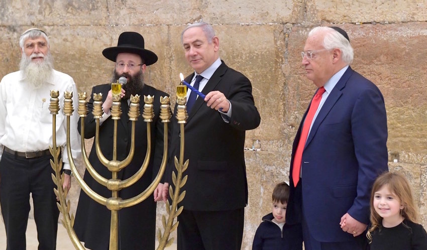 "Prime Minister Bibi Netanyahu and U.S. Ambassador to Israel David Friedman light the first Chanukah candle at the Kotel on Sunday. At left: Mordechai ""Suli"" Elias, Western Wall Heritage Foundation director and (with microphone) and Rabbi Shmuel Rabinovitch, Kotel rabbi."