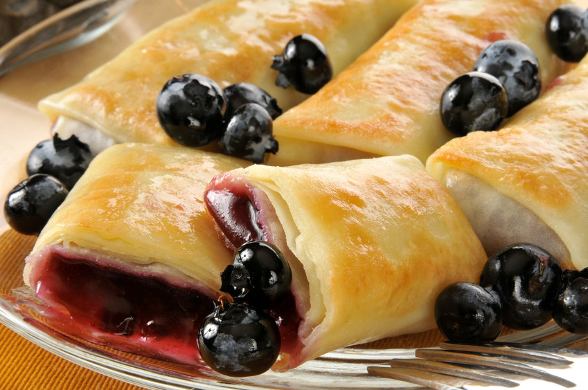 Closeup of golden blueberry blintzes or crepes with fresh berries.