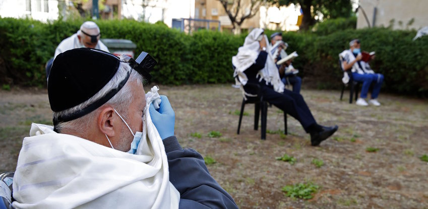 Men pray while keeping distance from each other outside their closed synagogue in Netanya, Israel, on April 23.