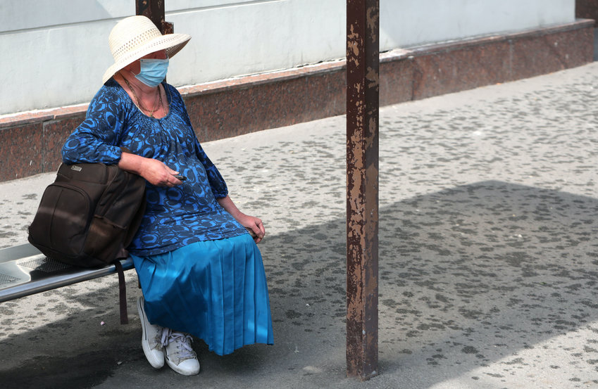 An elderly woman sits at a stop of public transport, Kyiv, capital of Ukraine.