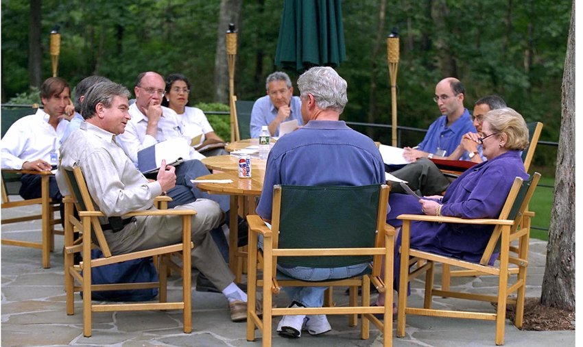 President Clinton with Secretary of State Madeleine Albright (right), National Security Advisor Sandy Ber- ger (left) and other staff, including former Mideast negotiator Aaron David Miller (back left) and Robert Malley (back right) at Camp David during Israeli-Palestinian negotiations in 2000.