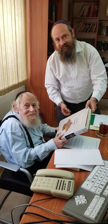 Rabbi Adin Even-Israel Steinsaltz and his son, Rabbi Meni Even-Israel and his father, inspect a newly printed volume of the Koren Noe Talmud series, an elegant and intuitive English-language edition of the Babylonian Talmud that is shaped by Rabbi Steinsaltz's acclaimed translation and commentary.
