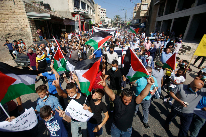 Palestinians hold flags during a rally in support of Palestinian President Mahmoud Abbas in the West Bank town of Tubas on Sept. 27.