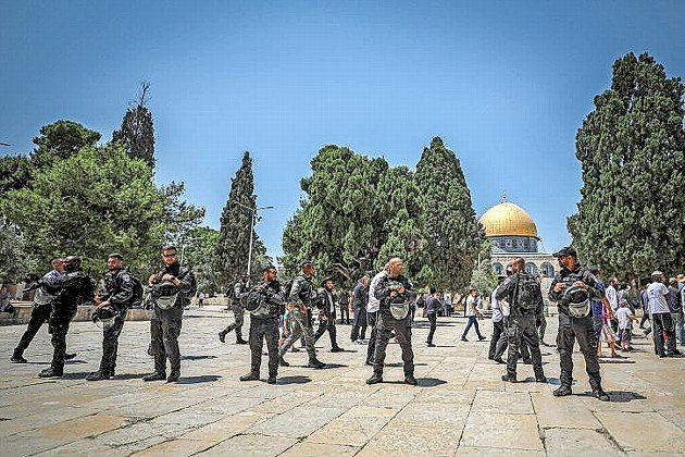 Israeli security forces stand guard as a group of Jews visit the Temple Mount during Tisha B'av, July 18.