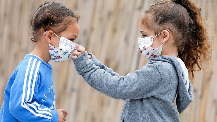 Israeli children adjusting their facemasks.