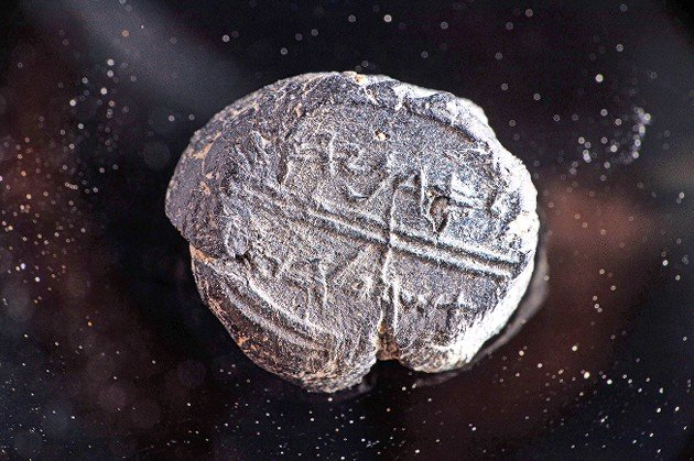 """This bulla, or seal, dating to the seventh century BCE, was found during an archaeological dig in Jerusalem's Old City. The seal bears the inscription """"Adoniyahu Asher Al Habayit."""" meaning """"Adoniyahu, Royal Steward."""""""