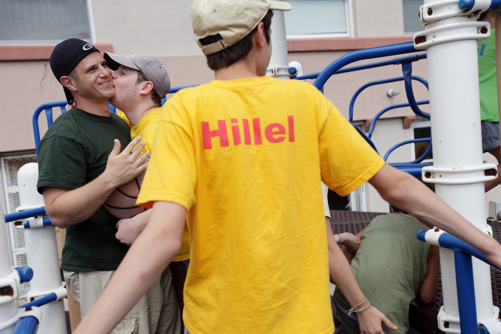 Ilan Blumstein, 20, second from left, gives his camp counselor Ben Mandel, 29, a hug at Hillel Day Camp, Thursday, July 22, 2010.
