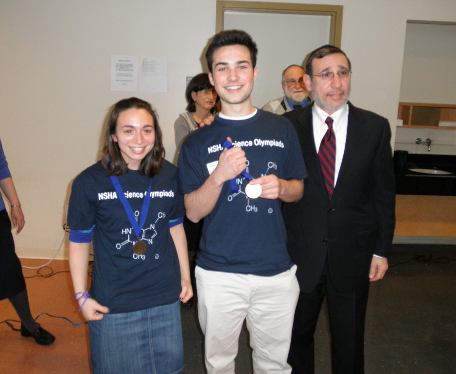 Ecology contest winners, NHSA students Amanda Goldstein and Brad Garczynski are awarded medals by Dean Dr. moshe Sokol of Lander College for Men.