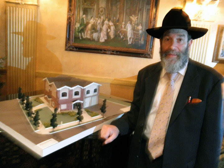 Hatzalah coordinator Rabbi Elozer Kanner stands with a model of the proposed Woodmere garage and training center.