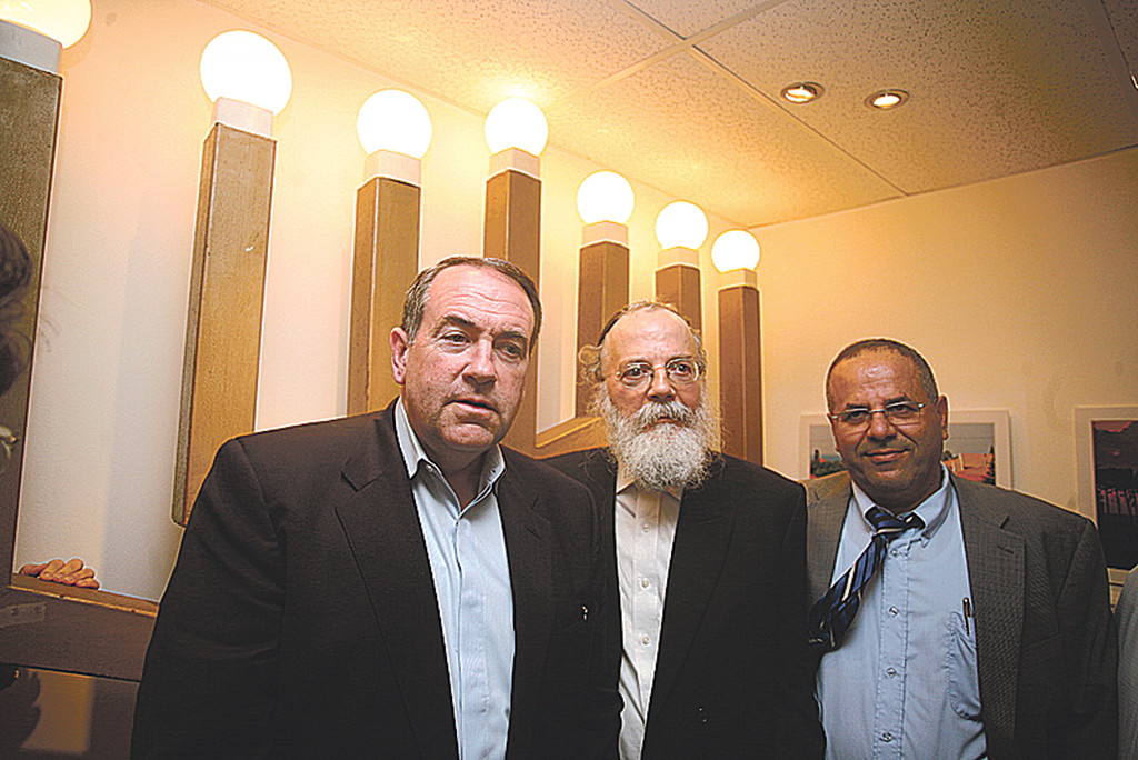 Gov. Mike Huckabee, Rabbi Sholom Dov Ber Wolpo, president of Gush Katif Museum, Deputy Minister Ayoub Kara, at museum in 2009 in front of the menorah from the shul in Netzarim.