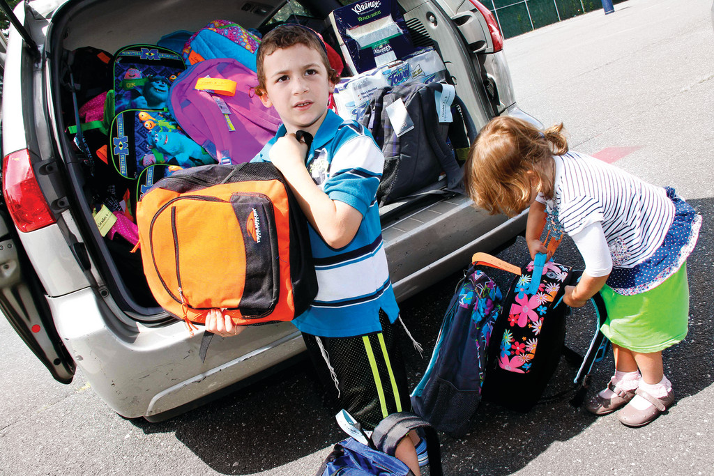 Siblings Akiva and Shira Laya Krasnovsky help load a car with backpacks.