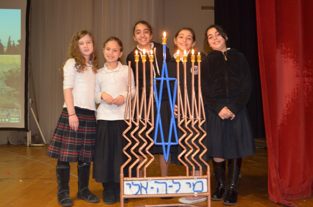 Five Shulamith students bask in the glow of the Chanukah lights at a school assembly.