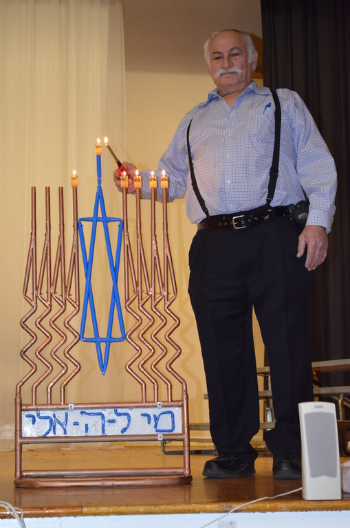 Gideon Gur Aryeh lights the   copper pipe menorah he created, on the stage at Shulamith School for Girls in Flatbush.