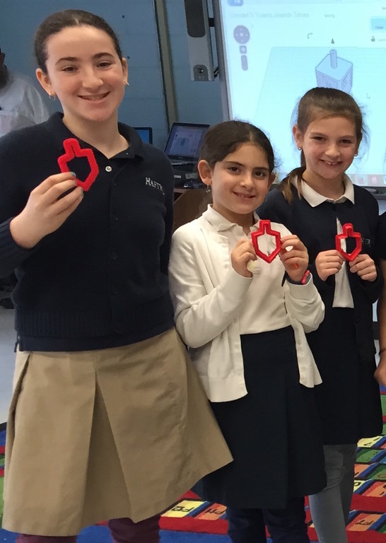 HAFTR lower school students hold dreidel-shaped cookie cutters created in class using a 3-D printer.
