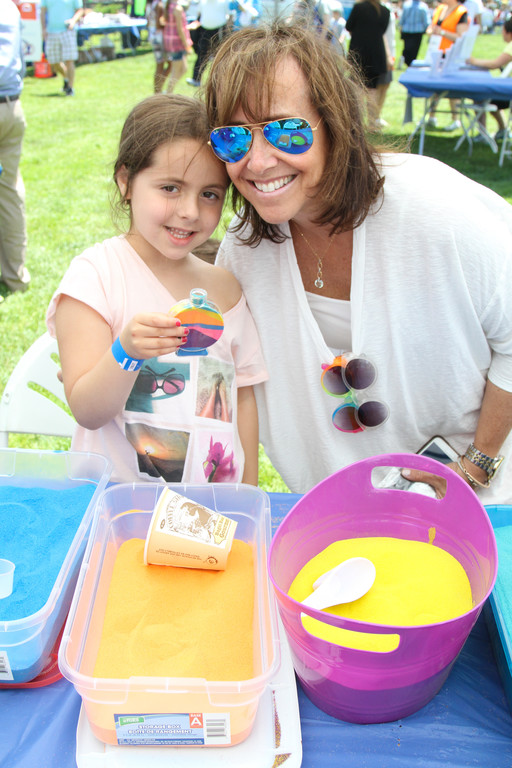 Fun with sand, Elianna Hercman helps Aviva Weber 5 with filling up her sand art.
