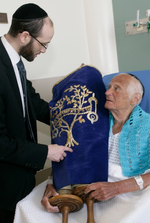 Rabbi Rachmiel Rothberger hands the 1880 torah scroll to Arthur Fisher, a patient at Calvary Hospital