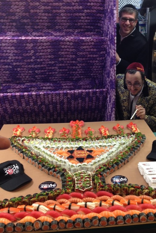 "Lipa pretends to light a candle on the ""world's largest sushi menorah,""  as Gourmet Glatt General Manager Yoeli Steinberg looks on, in 2013."