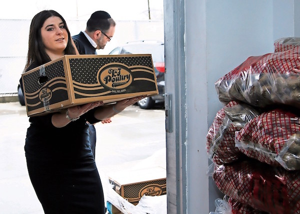 Tali Lebenbom and Rabbi Yehoshua Marchuck unload boxes at the JCC food pantry.