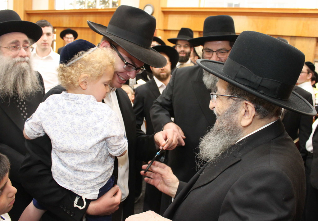 Rav Shmuel Kamenetsky cuts some hair off the son of Rabbi Pesach Horowitz, a member of Darchei Torah's Kollel Tirtza Devorah, in honor of his upsherin.