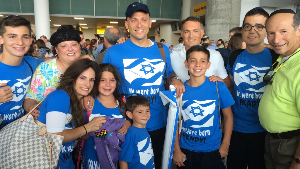 "Blue-shirted Samters of North Woodmere ""were born ready!"" to make aliyah, and now their time has come. They're pictured with just a few of the many relatives who came to JFK to see them off. From left: Avi, Teena, mom Bayla, Sophie, Dovi, dad Yehuda and Elisha Samter, Chaim Maza, and Moshe and Michael Samter. Bayla and Yehuda  grew up in Oceanside."