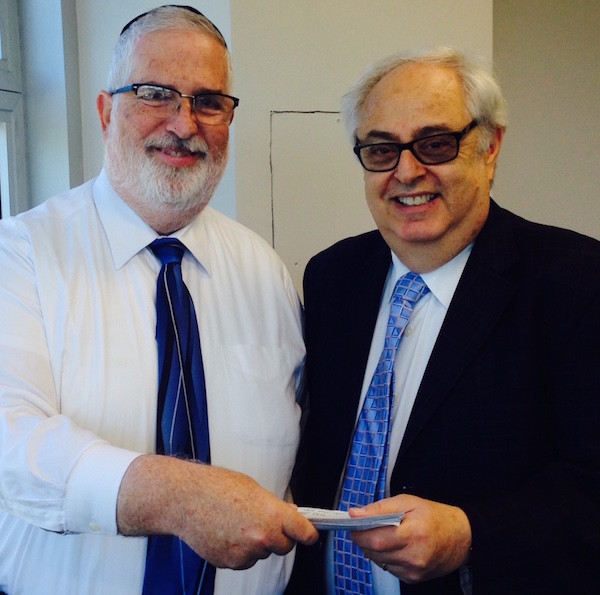 Dr. Shmuel Reisbaum of the Torah Academy for Girls presents a check to Irwin Gershon, senior development executive for New York's UJA-Federation.