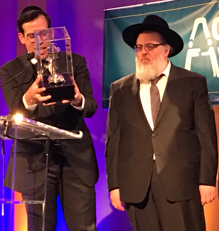 Rabbi Boruch Ber Bender reading the inscription on the Rabbinic Leadership Award presented to Rabbi and Mrs. Elysha Sandler.