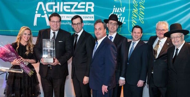 From left: Guests of Honor Pessi and Avi Goldstein, Achiezer Founder and President Rabbi Boruch Ber Bender, Achiezer Chairman Shulie Wollman, Dinner Chairman Dovid Bloom, Journal Chairman Aroni Parnes, Achiezer Trustee Ronald Lowinger, and Rabbi Yaakov Feitman of Kehillas Bais Yehuda Tzvi in Cedarhurst.