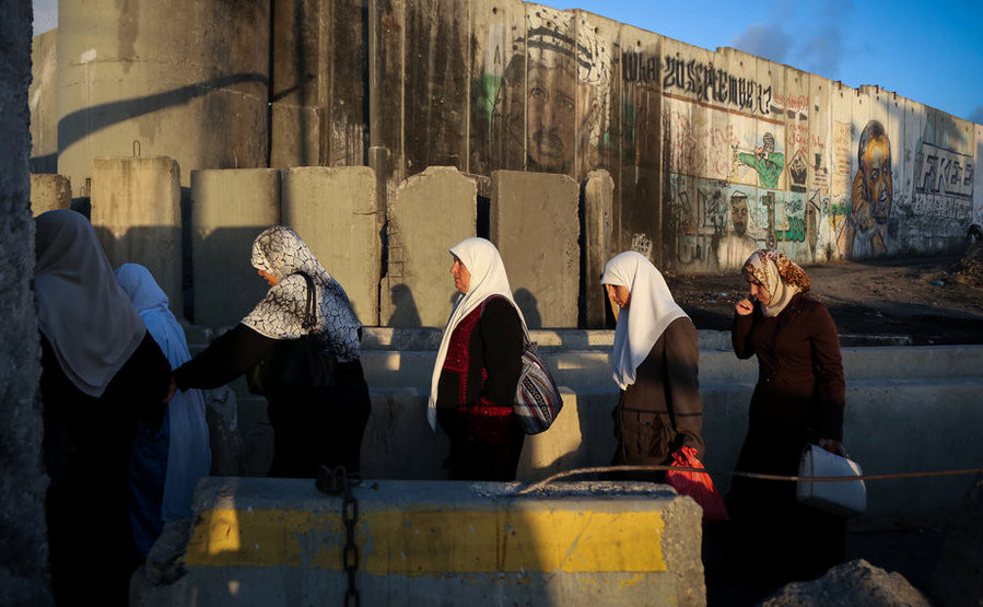 Palestinians cross the Qalandiya checkpoint, outside Ramallah, as they head to the Al-Aqsa mosque compound in Jerusalem, on June 10, 2016.