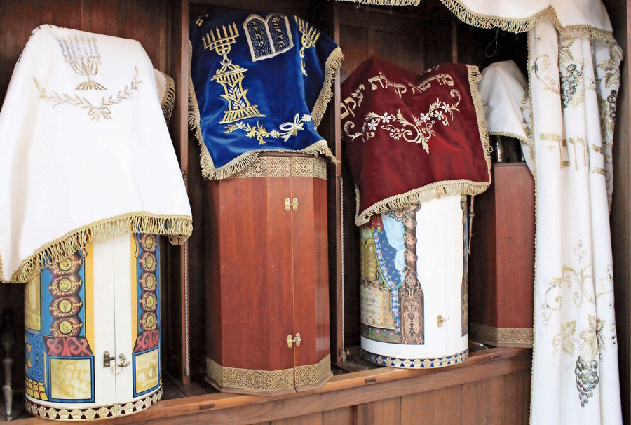 Karaite Torah scrolls are done in the Eastern style, with the scroll enclosed in a hard case.