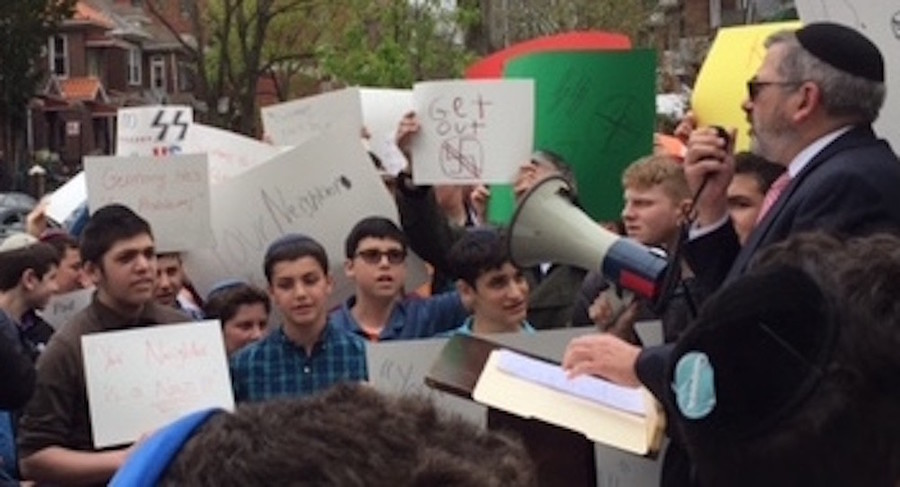 Rambam's dean, Rabbi Zev Meir Friedman, addresses his students at site of protest in Queens.