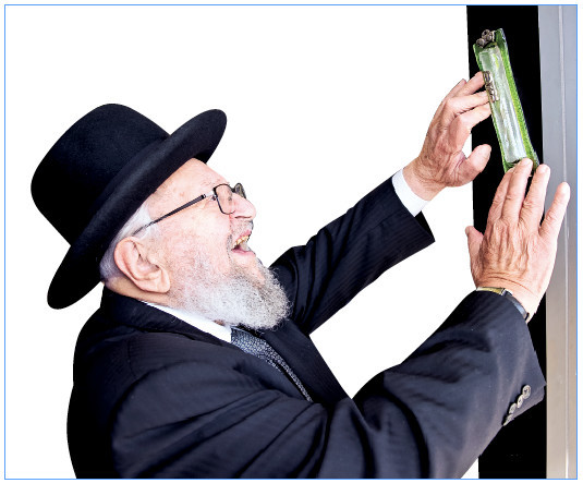 Rav Kamenetzky affixed a mizuzah at the 2015 grand opening of Gourmet Glatt in Woodmere. As the number of observant Jews grew, the number of kosher markets grew as well.