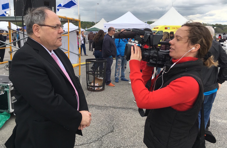 At Israelfest in Port Washington, Dani Dayon, Israel's counsel general in New York, reminds a reporter for Swiss television that Yom HaAtzmaut recognizes Israel rebirth in 1948 and not its founding thousands of years ago.