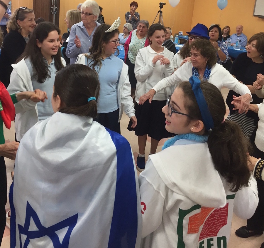 "Shulamith celebrates with seniors: Eighth graders went to the Five Towns JCC for a pre-Yom HaAtzmaut celebration with local seniors. The blue-and-white clad girls bantered and danced with the seniors, and joined in a spirited rendition of ""Happy Birthday"" for a woman celebrating her 100th."