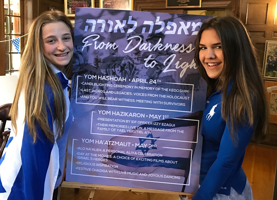 SKA girls flank a poster that explains the 3 days: Yom HaShoah, Yom Hazikaron, and Yom HaAtzmaut.