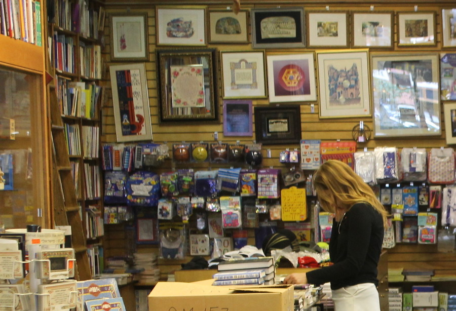 A shopper browses in book-lined Westside Judaica, which is set to close.