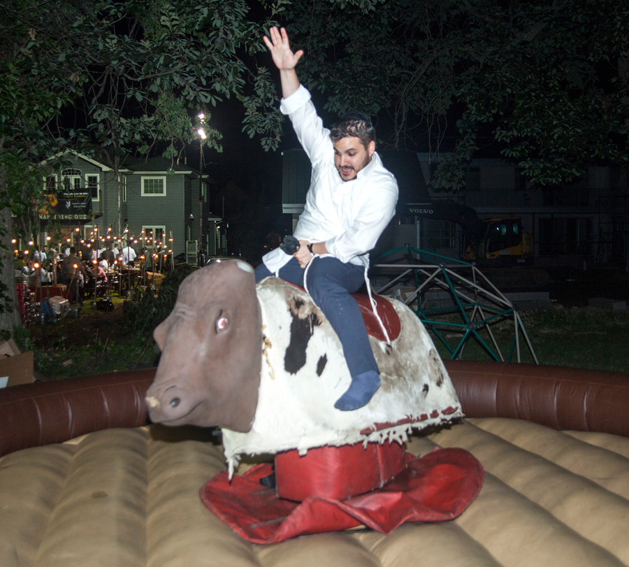 Machi Reichenberg, from Jerusalem, rides a mechanical bull.