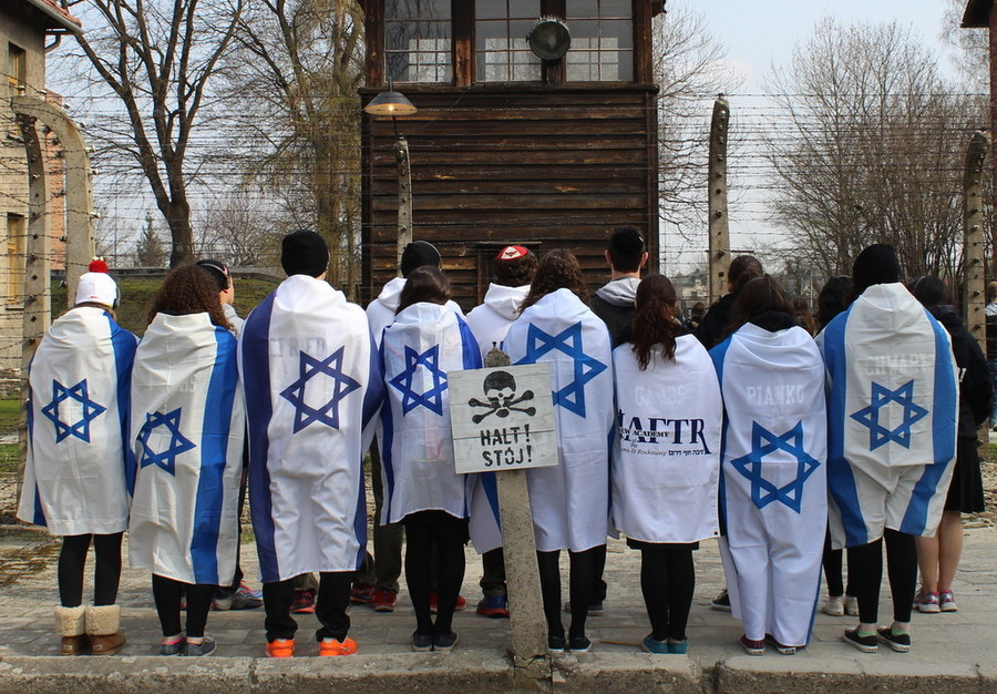 Students wrapped in Israeli flags at a concentration camp fence during a HAFTR HS trip to Poland in 2014.