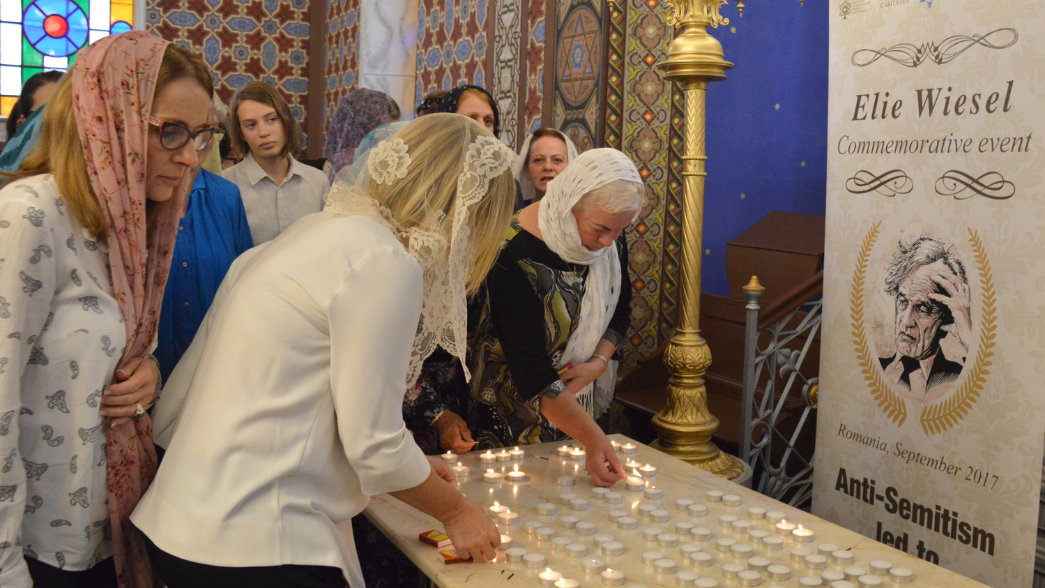 Women lighting candles in memory of Elie Wiesel at the synagogue in Ordea, in northern Romania, on Sept. 8.