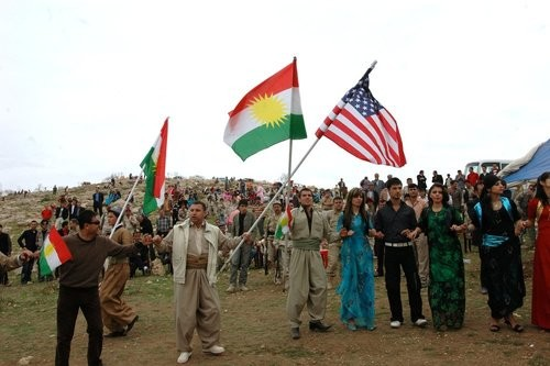 Local citizens wave Kurdish and American flags in Dahuk.