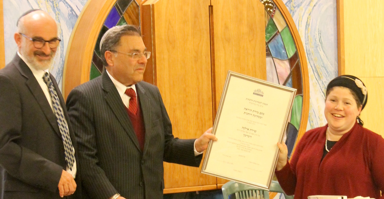 Rabbi Shuki Reich, left, seminary head of the Susi Bradfield Women's Institute of Halakhic Leadership, and Rabbi Shlomo Riskin, chancellor of Ohr Torah Stone, present Rabbanit Shira Zimmerman with her certification as a spiritual leader and arbiter of Jewish law at a ceremony in Jerusalem on Jan. 3.