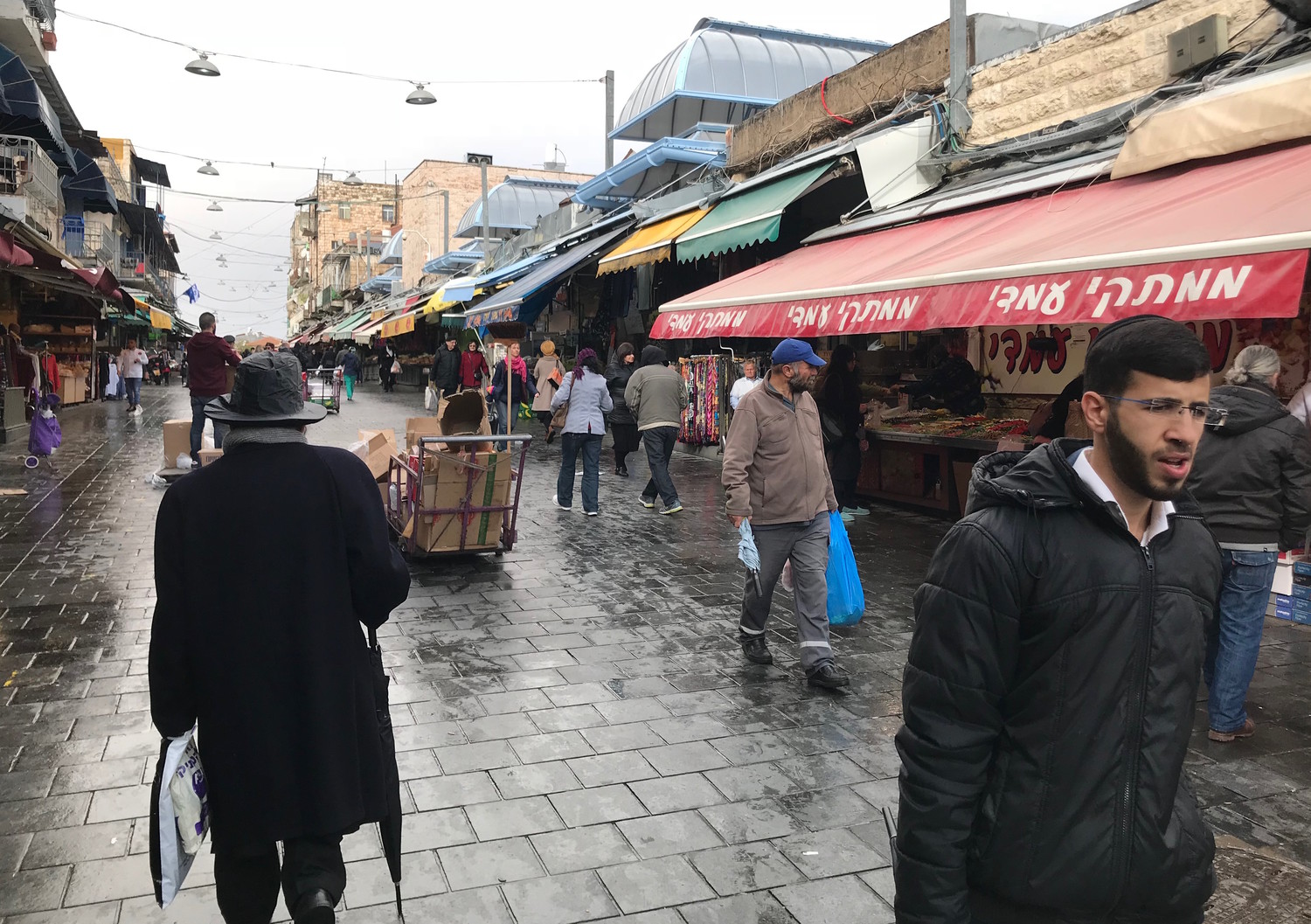 People shopping in the rain at the Mahane Yehuda market in Jerusalem, Dec. 6, 2017.