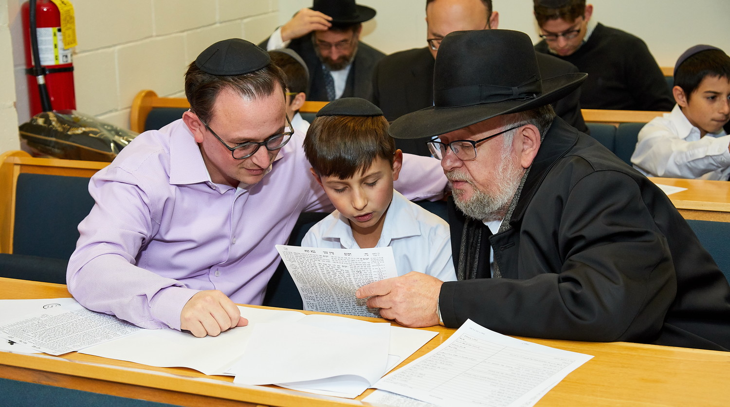Meir Katz, a fifth grader at Yeshiva of South Shore, is accompanied by his father and grandfather at a multi-generational celebration of his class' Haschalas Gemarah.