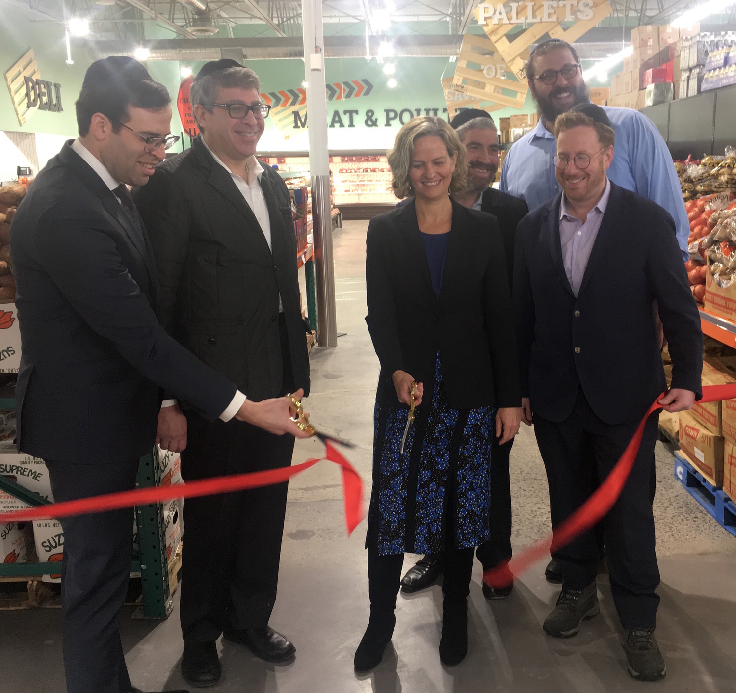 As the ribbon is cut at the opening of KolSave Market on Monday, Nassau County Executive Laura Curran is flanked (from left) by Achiezer Founder and President Rabbi Boruch Ber Bender, Gourmet Glatt's Yoeli Steinberg, Howie Klagsburn and Moshe Ratner, and (in back at right) KolSave store manager Mendy Herz.