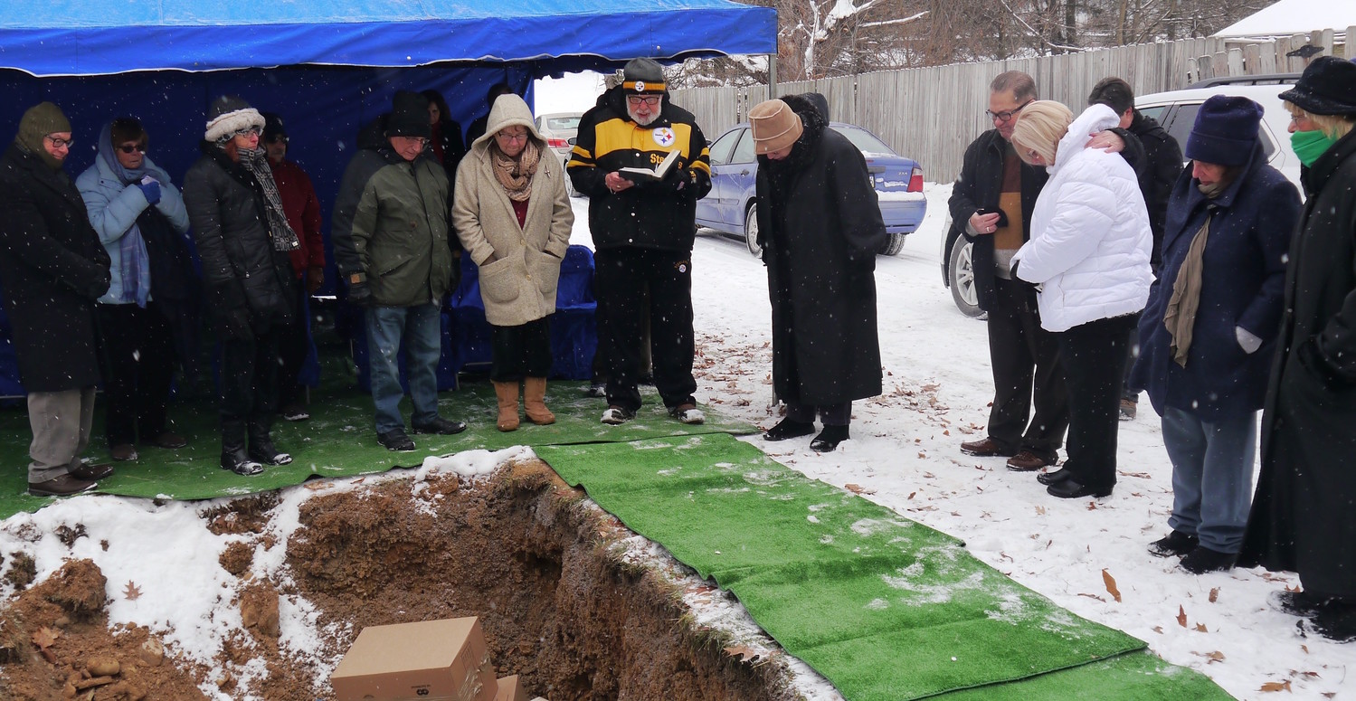 Congregants from Temple Hadar Israel in New Castle, Pa., gathering at the local Tifereth Israel cemetery to bury ritual objects from their defunct synagogue.