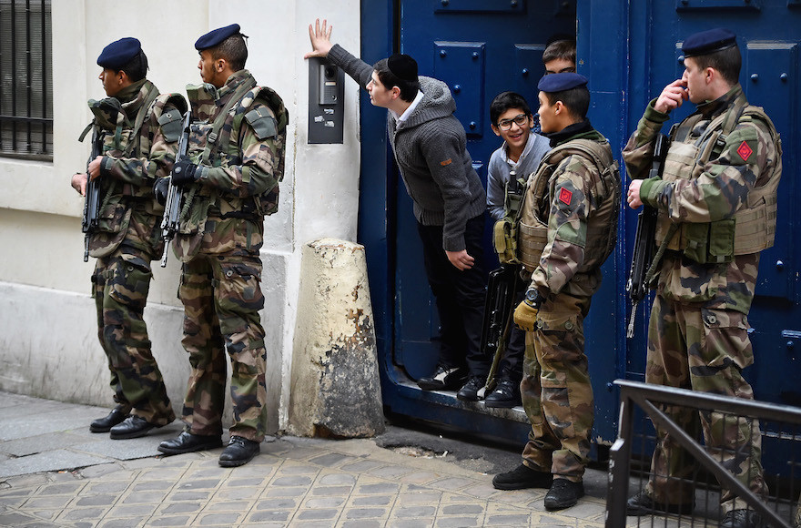 Children look out from a doorway as armed soldiers patrol outside a School in the Jewish quarter of the Marais district of Paris on Jan. 13, 2015.