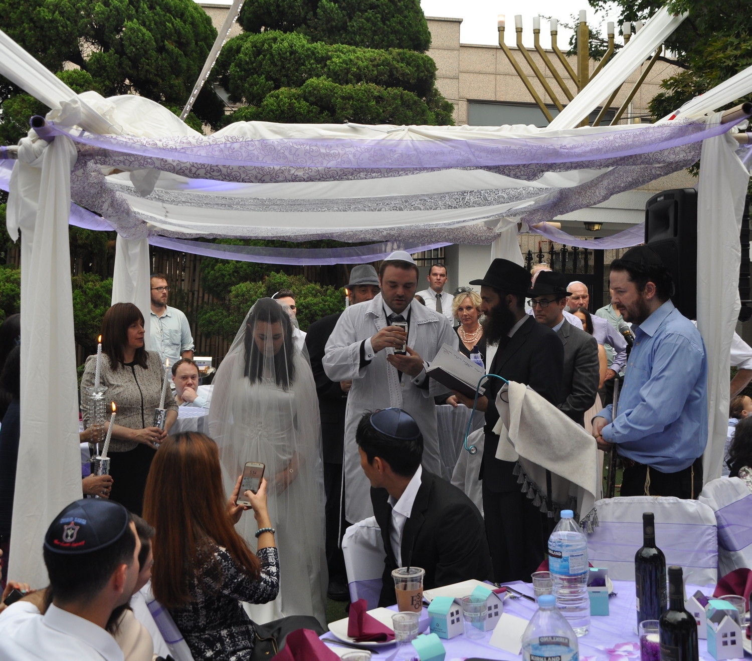 Rabbi Osher Litzman, under chuppah in black, performing a Jewish wedding in Seoul.