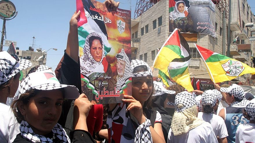 Palestinians hold posters showing terrorist Dalal Mughrabi.
