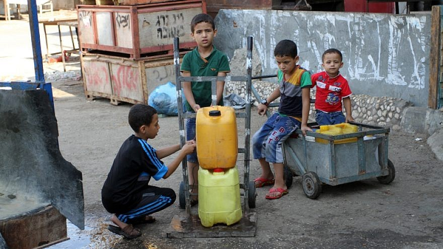 Palestinians fill plastic bottles and jar cans with drinking water from a public tap in the southern Gaza Strip refugee camp of Rafah, on July 26, 2015.