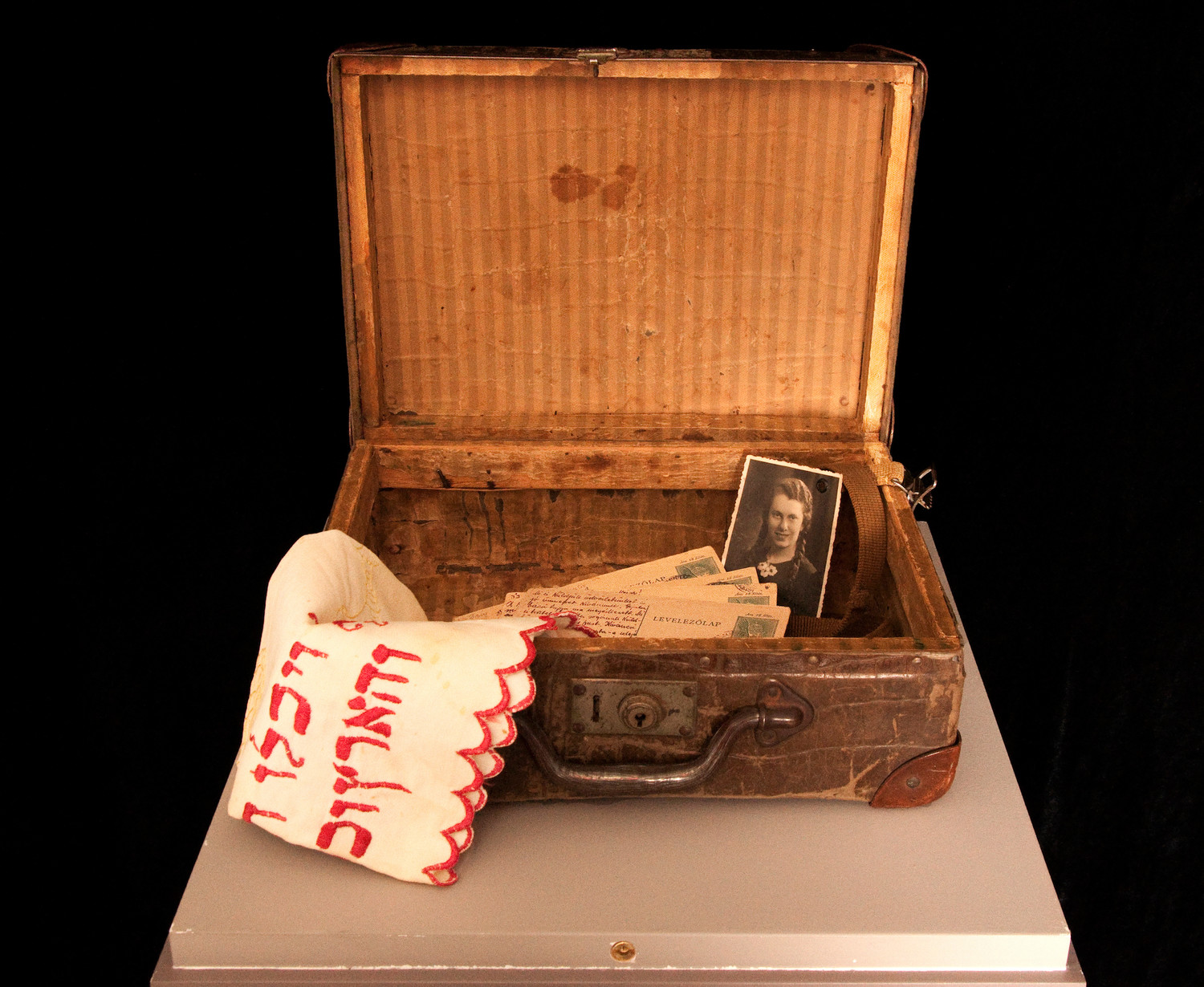 A small suitcase taken to the Budapest ghetto by a family named Horowitz, holding family photos, postcards and a challah cover, on display at the Amud Aish Memorial Museum.